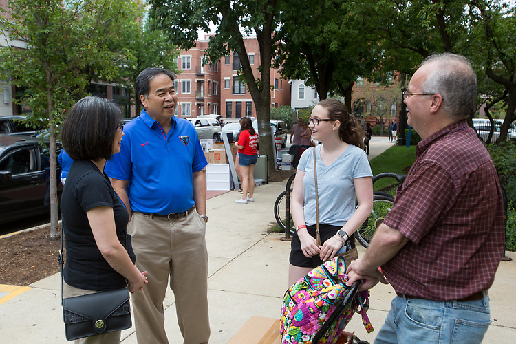 DePaul President A. Gabriel Esteban, Ph.D., and his wife, Josephine, talk with freshman Natalie Esh and her dad Andrew Esh during Move In Day.  Photo by Diane M. Smutny