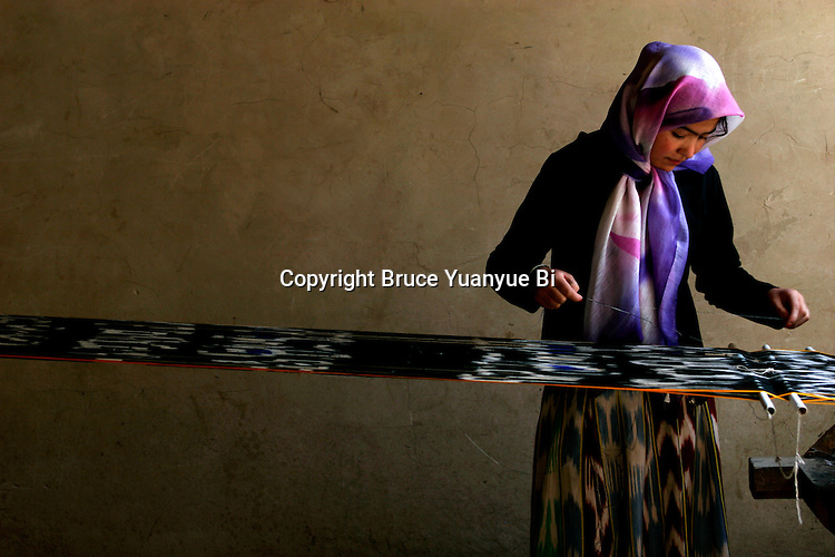 A young Uyghur girl weaving silk fabric in a local traditional workshop, Hotan, Xinjiang Province, China