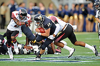 24 September 2011:  FIU quarterback Wesley Carroll (13) attempts to evade ULL cornerback Jemarlous Moten (2) and linebacker Devon Lewis-Buchanan (11) while rushing for a first down in the first quarter as the University of Louisiana-Lafayette Ragin Cajuns defeated the FIU Golden Panthers, 36-31, at FIU Stadium in Miami, Florida.