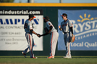 San Jose Giants outfielders Johneshwy Fargas (49), Sandro Fabian (54), and Bryce Johnson (28) celebrate after a California League game against the Modesto Nuts at John Thurman Field on May 9, 2018 in Modesto, California. San Jose defeated Modesto 9-5. (Zachary Lucy/Four Seam Images)