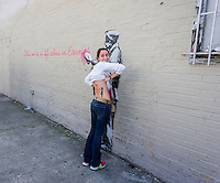 """A street art enthusiast shows off her Banksy inspired tattoo in the Woodside neighborhood of Queens in New York on Monday, October 14, 2013 in front of the fourteenth installment of Banksy's graffiti art, """"What we do in life echoes in Eternity"""". The elusive street artist is creating works around the city each day during the month of October accompanied by a satirical recorded message which you can hear by calling the number 1-800-656-4271 followed by  # and the number of artwork.  (© Richard B. Levine)"""