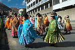 Dancing cholitas, dressed in the traditional indigenous Aymaran clothing of bowler hats, mantas or shawls amd pollera dresses, celebrate a religious festival through the streets of La Paz, Bolivia.