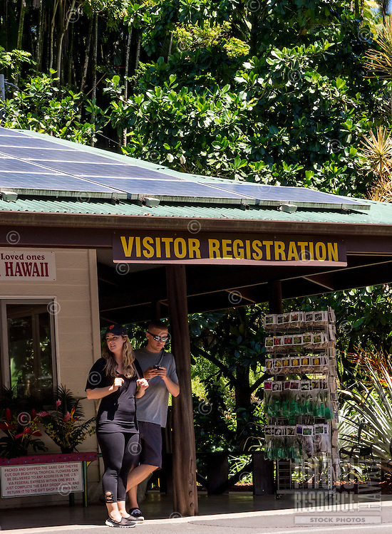 Visitors at the visitor registration sign and gift shop of the Hawaii Tropical Botanical Garden, Papa'ikou, Big Island of Hawaiʻi.