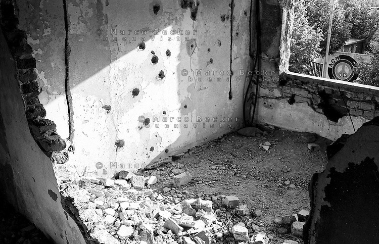 Mostar, un edificio in rovina, danneggiato durante la guerra. Fori di proiettile nel muro e un simbolo della pace all'esterno, --- Mostar, the ruin of a building damaged during the war. Bullet holes in the wall and a peace sign outside