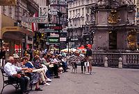 Vienna, Austria, Wien, People sitting on bench in the plaza on Graben Street in downtown Vienna.