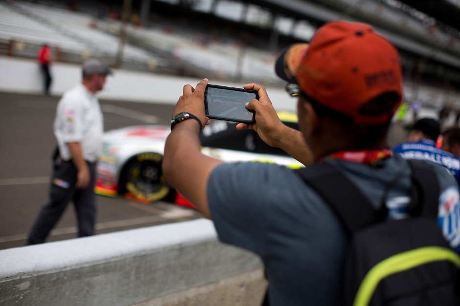 A fan leans over a barrier to photograph Jeff Gordon's car before the Brickyard 400 on Sunday, July 26, 2015, at the Indianapolis Motor Speedway. (Photo by James Brosher)