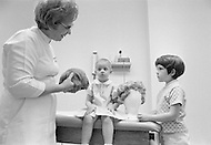 August 1971, Memphis, Tennessee, USA --- A leukemia patient is assisted by a nurse in the wig room. After radiotherapy children need to wear a wig for a few months before their hair grows back. Founded by Lebanese actor Danny Thomas, the hospital was the first to cure leukemia in children (Acute Lymphocytic Leukemia) in 1971. --- Image by © JP Laffont