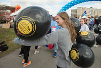 NWA Democrat-Gazette/BEN GOFF @NWABENGOFF<br /> Taylor Shapley of Bentonville hands out balloons to children at the finish line Saturday, April 14, 2018, during the American Heart Association's annual Northwest Arkansas Heart Walk at the Walmart AMP in Rogers. Area participants in the American Heart Association's Sweethearts program for high school girls were volunteering to hand out balloons at the finish line.