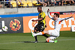 Brisbane Roar's Corey Brown, right, throws out a leg in an attempt to stop a shot by Phoenix's Roly Bonevacia, left, in the A-League football match at Westpac Stadium, Wellington, New Zealand, Sunday, January 04, 2015. Credit: Dean Pemberton