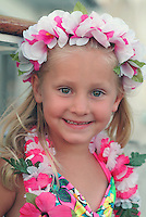 Portrait of a young girl ( 5) vacationing in Hawaii wearing leis