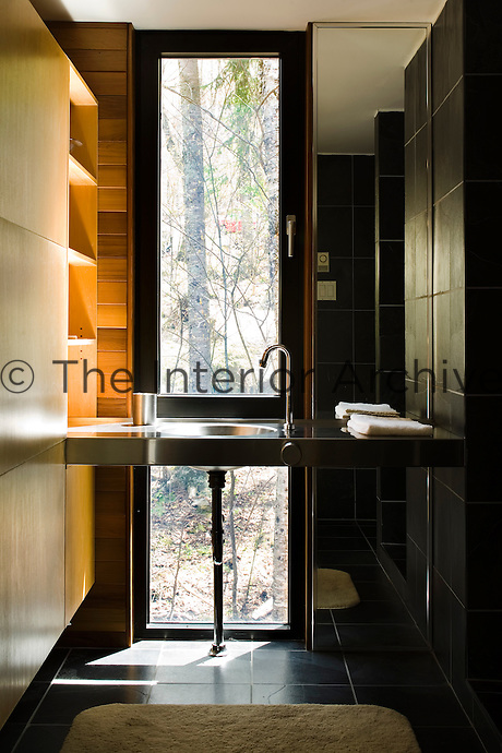 A stainless steel wash basin in this black-tiled bathroom is illuminated by a floor-to-ceiling window with a view over the surrounding woodland