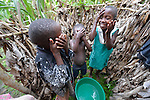 Children bathe in the morning in Lukaya, Uganda, where the Good Samaritan Women's Project has helped rural women improve their financial literacy, thus improving the quality of life for the women, many of whom are widows who also care for children who lost their parents to AIDS. The program was funded by the Call to Prayer and Self-Denial of United Methodist Women. These children belong to an extended family, where a widow with three children has adopted four children of her sister who died.