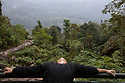 India - Sikkim - A young girl drying her hair in the wind at a natural hot springs located in the forest.
