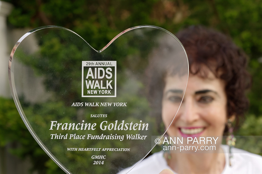 Merrick, New York, USA. May 3, 2018. Francine Goldstein poses with one of many appreciation trophies she's received from AIDS WALK NEW YORK, a fundraising walk and run in Central Park.