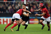 Dan Carter of New Zealand is tackled in possession. Rugby World Cup Pool C match between New Zealand and Tonga on October 9, 2015 at St James' Park in Newcastle, England. Photo by: Patrick Khachfe / Onside Images