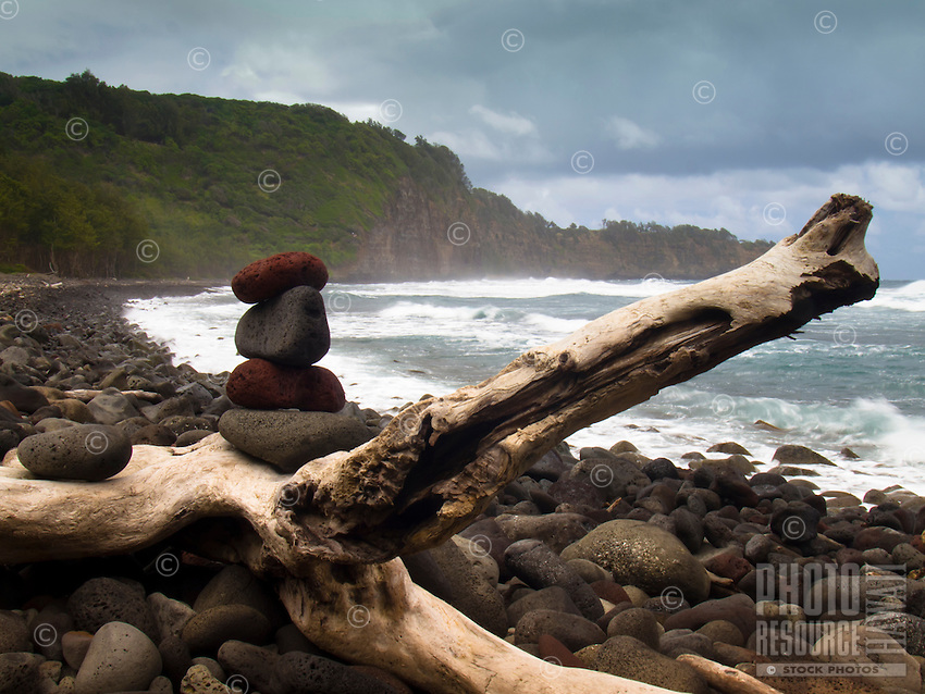 Stones stacked on a large piece of driftwood on the black sand beach of Pololu Valley, North Kohala, Big Island.