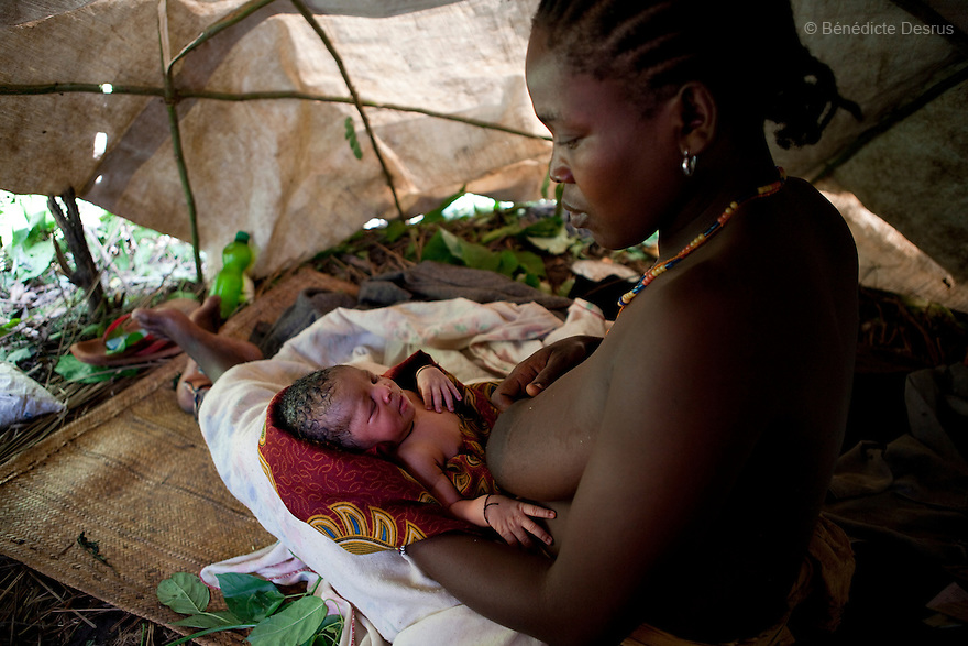 25 may 2010 - Western Equatoria State, South Sudan - A woman who gave birth on may 24, 2010 while fleeing the LRA. She holds her newly born baby in a makeshift tent near a road in Diabio (38 miles from Yambio), South Sudan. A spate of continuing LRA attacks in Western Equatoria State has pushed thousands of families to flee from their remote homes to larger towns and along roadsides to seek protection. Western Equatoria state has been rocked by LRA activities since 2006. Photo credit: Benedicte Desrus
