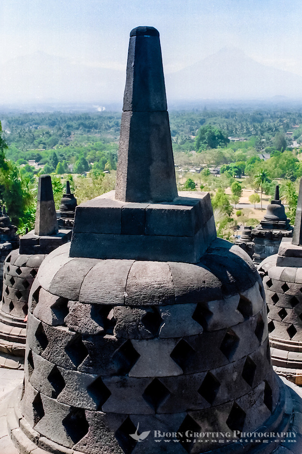 Java, Central Java, Borobodur. The three upper circular terraces carries 72 stupas, of which most contains a Buddha statue. The mount Merapi volcano in the background.