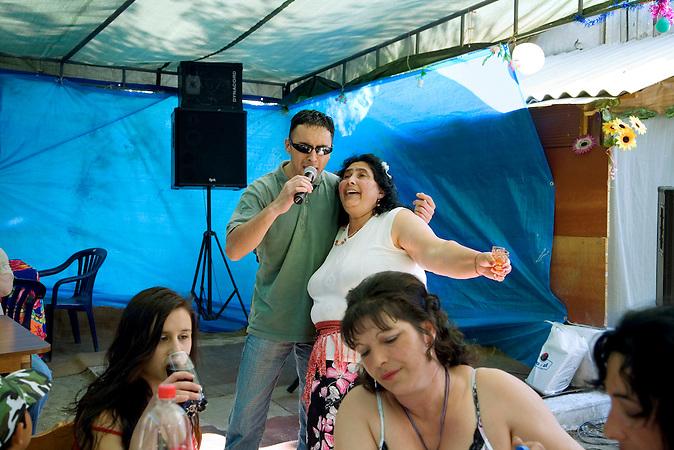 Tornjos, Vojvodina, Serbien, 29.04.2007: Auf der Geburtstagsfeier eines Roma-Jungen singt die Grossmutter Arm in Arm mit einem Saenger. In der Hand haelt sie zwei Glaeser Rakija.<br /> Tornjos, Vojvodina, Serbien, 29.04.2007: At a Roma boy's birthday party, the grandmother sings along with a singer while holding to glasses of Rakija.<br /><br />[ CREDIT: www.throughmyeyes.de - Merlin Nadj-Torma - phone +49-177-8279119 - merlin@throughmyeyes.de ]