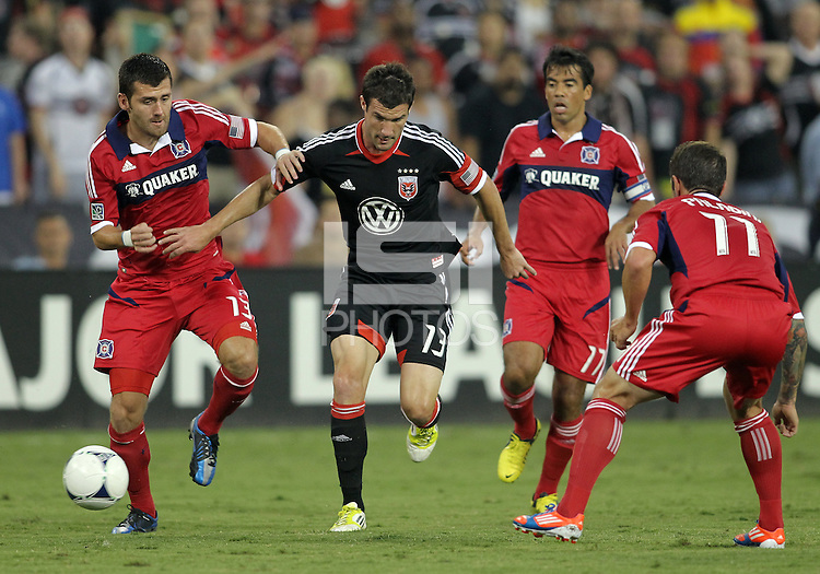 WASHINGTON, DC. - AUGUST 22, 2012:  Chris Pontius (13) of DC United tries to get past  Gonzalo Segares (13) and  Daniel Paladini (11) of the Chicago Fire during an MLS match at RFK Stadium, in Washington DC,  on August 22. United won 4-2.