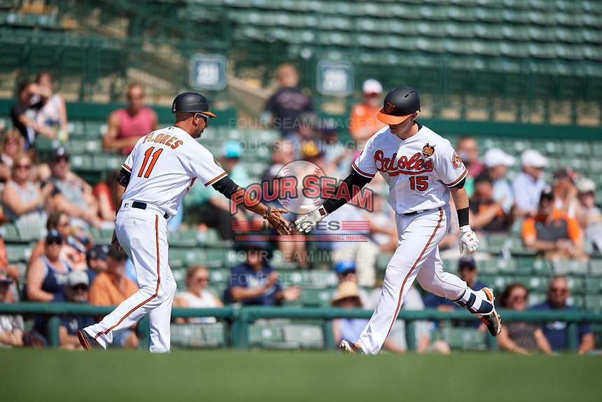 Baltimore Orioles catcher Chance Sisco (15) is congratulated by third base coach Jose David Flores (11) as he rounds third base after hitting a home run in the bottom of the second inning during a Grapefruit League Spring Training game against the Tampa Bay Rays on March 1, 2019 at Ed Smith Stadium in Sarasota, Florida.  Rays defeated the Orioles 10-5.  (Mike Janes/Four Seam Images)