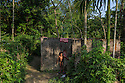 India – West Bengal: A kid standing outside a washing point in Pakka Line, one of the villages dotting the Mogulkata Tea Estate, in the Dooars region. Although companies are obliged to provide workers with houses, discounted food rations, schooling, water and health facilities, these services are often non-existent or not up to the standard.