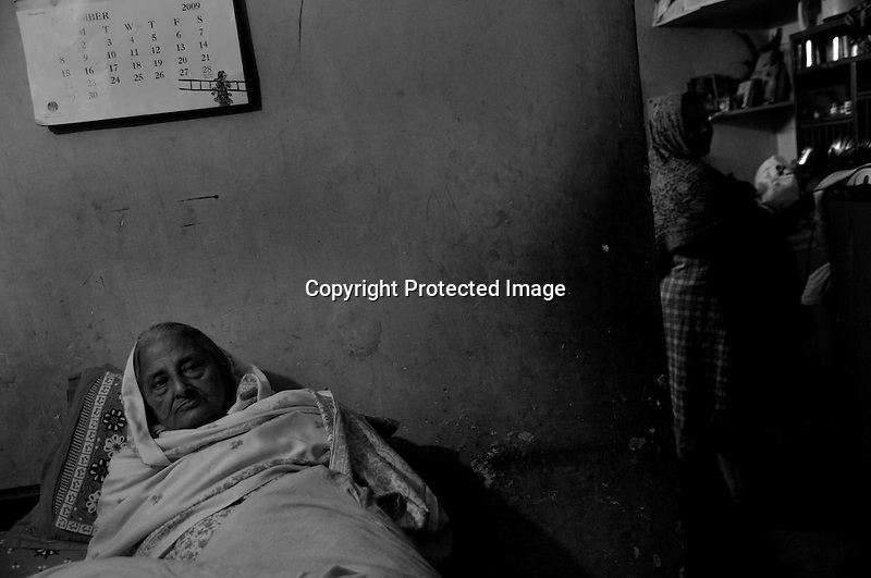 Sarjeet Kaur lost her husband in the Sikh Genocide in 1984. His only son who was bitten badly now walks with the support of a stick and gets spinal chord aches at night. She was traumatized and ever since has remained sick, suffering even after 25 years of the incident. Tilak Vihar in New Delhi is called the widow colony. Widows and children of the Sikhs who were killed in 1984 Sikh Genocide live here. Four thousand Sikhs were killed in 72 hours in Delhi alone but no body till date has been punished for such an inhuman crime. Illiteracy, drug addiction, child labour and immense poverty characterize the area. Twenty five years ago all the male family members above the age of 15 were killed and burnt, leaving their uneducated widows and children behind to suffer, even after 25 years. The present generation is jobless, steeped in alcoholism and have lost their directions in life. November 2009. New Delhi, India, Arindam Mukherjee