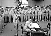 Gen. Douglas MacArthur signs as Supreme Allied Commander during formal surrender ceremonies on the USS MISSOURI in Tokyo Bay.  Behind Gen. MacArthur are Lt. Gen. Jonathan Wainwright and Lt. Gen. A. E. Percival.  September 2, 1945.  Lt. C. F. Wheeler. (Navy)