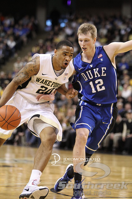 Wake Forest Demon Deacons forward Ari Stewart (20) drives the basket with Duke Blue Devils forward Kyle Singler (12) looking to cut him off. Duke leads at halftime 41-32.