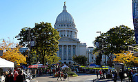 People cross in front of the Wisconsin State Capitol Building at the Dane County Farmers' Market on Saturday, October 17, 2015 in Madison, Wisconsin