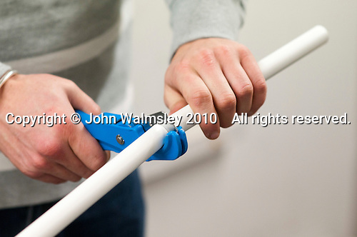 Student electrician cutting plastioc tubing to length, Able Skills, Dartford, Kent.