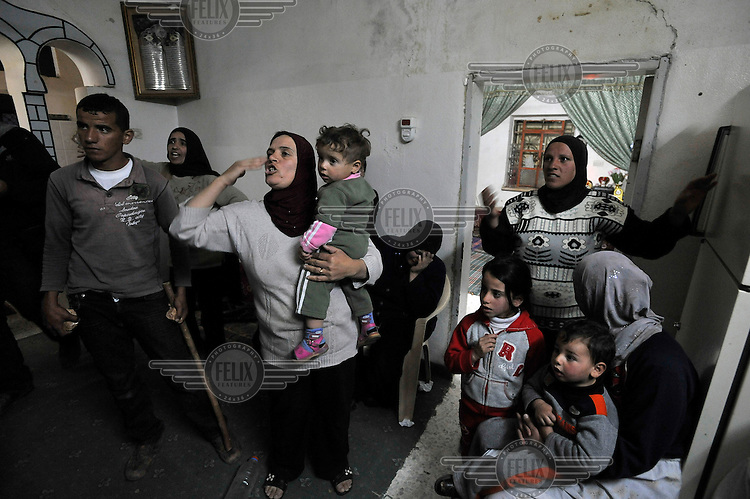Palestinians inside their house, as it is attacked by rioting Jewish settler youths. Violence erupted as the Israeli army evicted a group of settlers from a disputed building in Hebron. The Israeli high court had rejected the settlers' claim that they legally bought the house from its Palestinian owner. As the house became a symbol of defiance, the few families living there were joined by a mob of some 1,500 radical right-wing youths, who went on a rampage and attacked Palestinians in the mixed West Bank city.