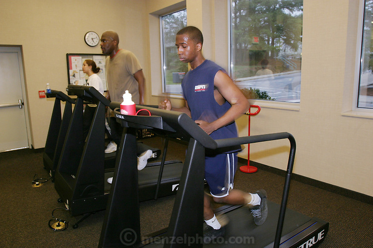 Every week, the Revis family (foreground, Brandon Demery, behind him is Ron) faithfully trekked to the health club in the Wakefield Medical Center in Raleigh, North Carolina, a hospital complex, for two-hour exercise sessions. They enjoyed the workouts, but found them so time-consuming that they wound up eating more fast food than ever. Fearing its potential impact on their health, they ultimately gave up the club in favor of dining and exercising at home. (Supporting image from the project Hungry Planet: What the World Eats.)