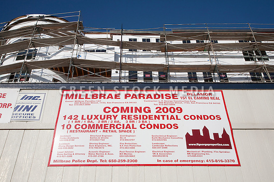 A low angle view of an advertising sign promoting a transit orientated housing development. The Millbrae Paradise mixed use construction project located on El Camino Real in Millbrae, CA is a great example of transportation oriented development (TOD) since it is located a very short walking distance from the Millbrae Transit Hub featuring Caltrain, BART, and bus mass transportation options ideal for both commuter and recreational uses. The project features 142 residential condominiums and 10 commercial condo spaces for restaurants or retail stores. Millbrae, California, USA