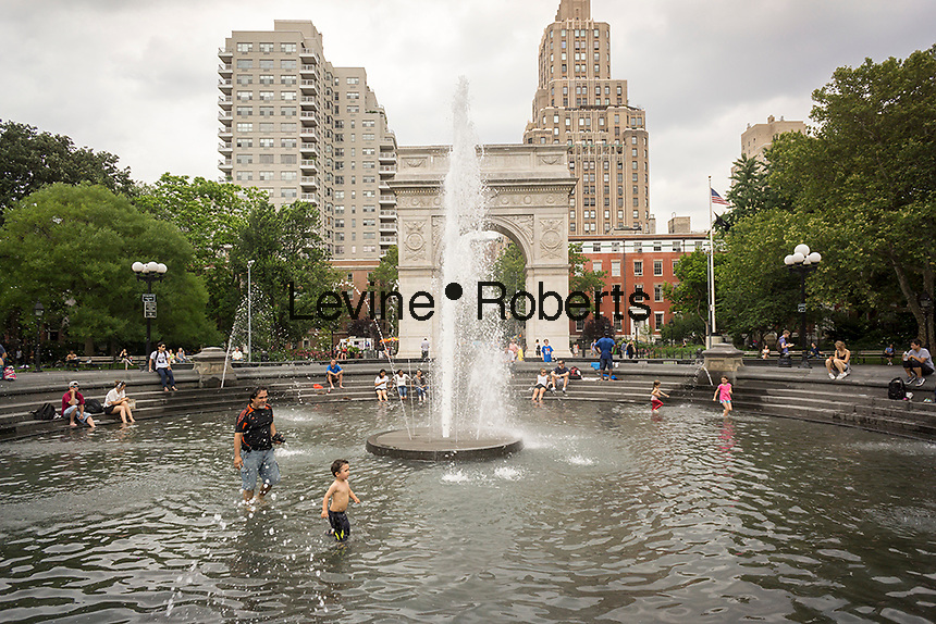 Sweltering New Yorkers and visitors dip into fountains, such as the one in Washington Square Park in Greenwich Village in New York on Tuesday, June 23, 2015. A heat advisory and thunderstorm watch are in effect in the city as temperatures rise to 88 F while the humidity makes it feel like 93 F. ( © Richard B. Levine)