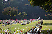 Japanese men walk between war graves after a Remembrance Day ceremony at the Yokohama War Cemetery, Hodogaya. Yokohama, Japan. Sunday November 9th 2014