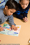 Education Preschool 4-5 year olds  art activity boy drawing with marker recognizable human figure another boy watching him work vertical