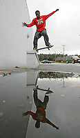Israel West is reflected in a puddle as he slides on his skateboard on  whatever Ave. Sunday in charlottesville, Va. Photo/The Daily Progress/Andrew Shurtleff