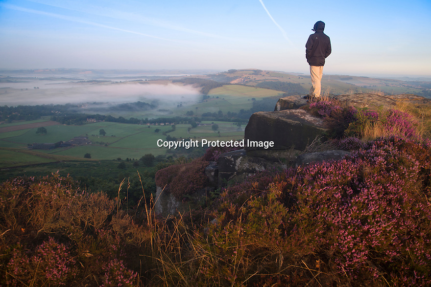 15/08/16<br /> <br /> A walker stops to admire the view. After a chilly night in the Peak District, low cloud blankets the stunning Derbyshire countryside as the sun rises over Curbar Edge this morning ahead of a forecast week of late summer hot weather.<br /> <br /> This type of weather phenomena is known as an inversion and can occur when, for example, a warmer, less-dense air mass moves over a cooler, denser air mass. This type of inversion occurs in the vicinity of warm fronts.<br /> <br /> All Rights Reserved, F Stop Press Ltd. +44 (0)1773 550665
