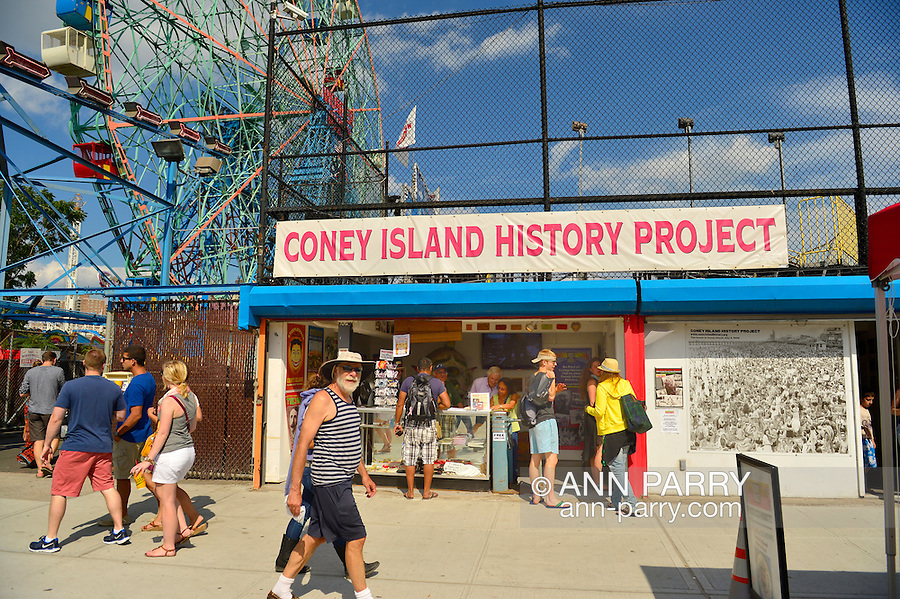Brooklyn, New York, USA. 10th August 2013. The Coney Island History Project banner is over the booth where visitors can get information about the world famous neighborhood, beach and boardwalk and amusement park, during the 3rd Annual Coney Island History Day celebration. The Wonder Wheel ride is at left in the background.