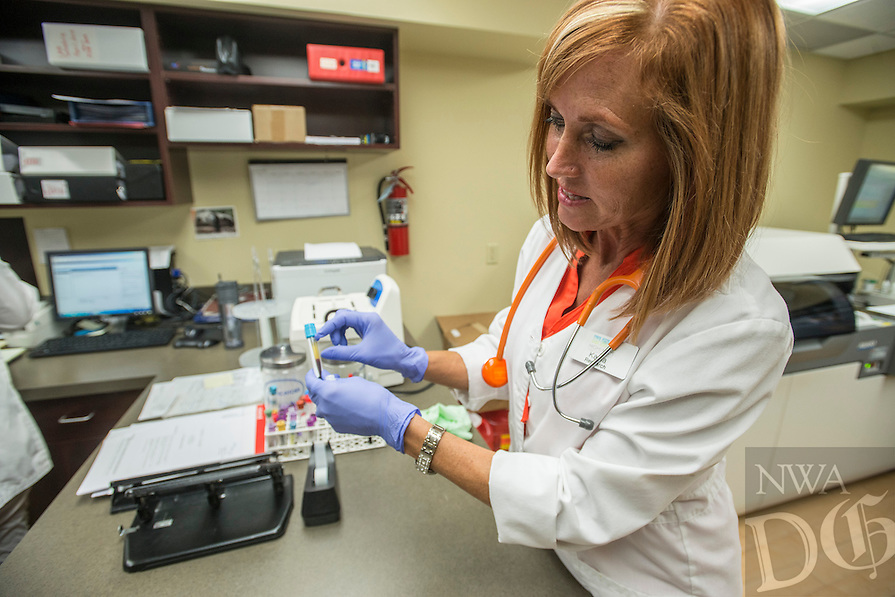 NWA Democrat-Gazette/ANTHONY REYES &bull; @NWATONYR<br /> Kayla Kelly, medical assistant for research, demonstrates Friday June 26, 2015 how she uses drawn blood to pull samples from to see how far along patients are in their treatments at Highlands Oncology Group in Fayetteville. The group is taking part in several research projects including one that will track about 80 patients in 40 active clinic research projects testing new cancer drugs and treatments.