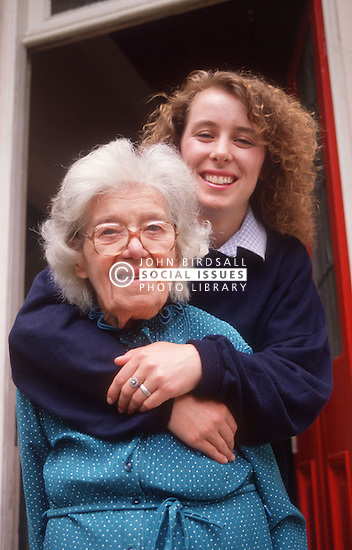 Elderly woman being hugged from behind by young carer wearing uniform,