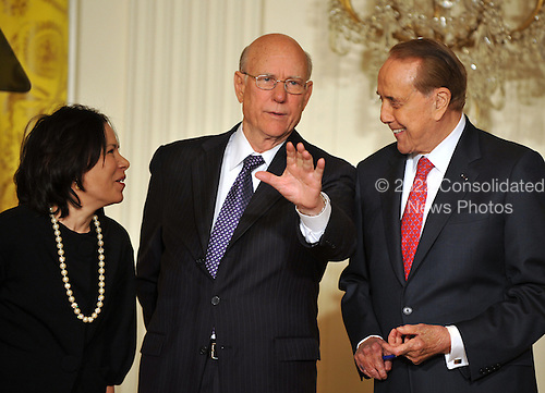 "Washington, D.C. - March 2, 2009 -- United States Senator Pat Roberts (Republican of Kansas), center, shares some thoughts with Nancy-Ann DeParle, just named Counselor to the President and Director of the White House Office for Health Reform, left, and Former United States Senator Bob Dole (Republican of Kansas), right as they await the arrival of United States President Barack Obama  in the East Room of the White House in Washington, DC on Monday, March 2, 2009.  Obama named Governor Kathleen Sebelius (Democrat of Kansas) as Secretary of the Department of Health and Human Services (HHS).  The President also announced the release of $155 million authorized by the American Recovery and Reinvestment Act (ARRA) that will support 126 new health centers.  In a release, the White House stated ""These health centers will help people in need - many with no health insurance - obtain access to comprehensive primary and preventive health care services."".Credit: Ron Sachs / Pool via CNP"
