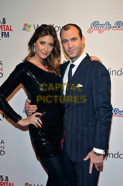 LISA SNOWDON & JOHNNY VAUGHAN.95.8 Capital FM Jingle Bell Ball at 02 Arena Greenwich, London, England 5th December 2009.half length black sequins sequined dress one shoulder hand ring on hip blue suit jacket pinstripe arm around waist .CAP/PL.©Phil Loftus/Capital Pictures.