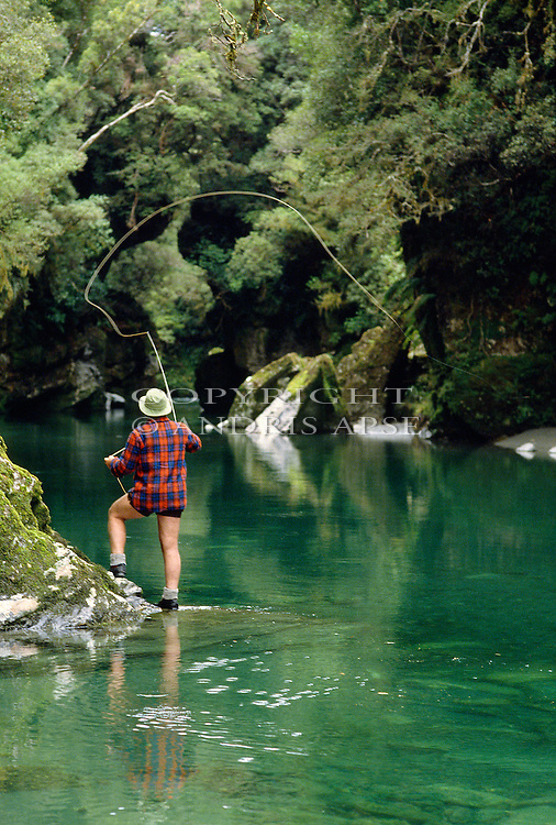Flyfishing in the Crooked River. Westland Region New Zealand. Vertical format.