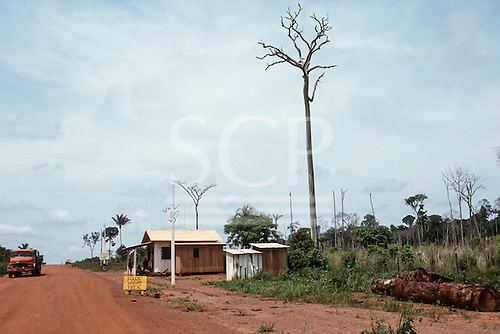 Mato Grosso State, Brazil. Government checkpoint on a dirt road in deforested area with dead and dying trees and tree trunks lying at the side of the road.