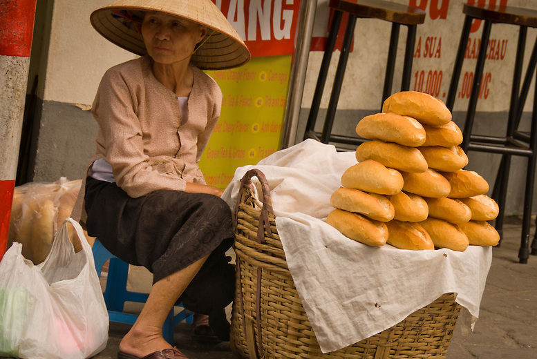 A woman sells French bread on the side of the road. The French occupied Vietnam for a century in the mid 1800's. The Vietnamese have incorporated some of the French traditions in their everyday life.