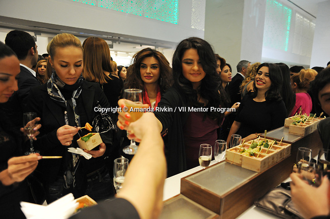 Young women drink cocktails, wine and champagne while snacking on sashimi from high end restaurant Chinar at the grand opening celebration of Emporium's second store at the Port Baku luxury residences in the Azeri capital of Baku, Azerbaijan on October 28, 2011. Emporium's second store in Baku was designed by Japanese architect Yukio Ishiyama of the Milanese design firm Garde and features over 150 luxury ready-to-wear brands such as Azzedine Alaïa, Marc Jacobs and Stella McCartney; Emporium is widely considered to offer the greatest variety of high-end designer shopping in Baku under one roof.