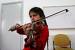 "FOR FAOIROUZ SONG ""THE FLOWER OF THE CITIES"" - A Palestinian girl plays the Violin during a lesson in the Edward Said National Conservatory of Music in East Jerusalem. Photo by Quique Kierszenbaum."