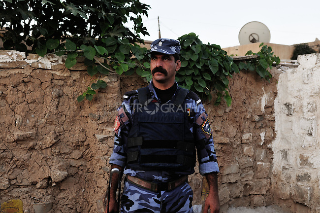 KIRKUK, IRAQ: An Iraqi policeman during raid in the Tawari neighborhood in central Kirkuk...Kirkuk, the oil-rich city in northern Iraq, is home to Kurds, Arabs, Turkomen, Christians, Kakayi, and numerous other ethnicities. Since 2003, thousands of its residents have been killed or injured in terrorist attacks...As the US military leaves Iraq, the future of this violent and ethnically diverse city remains unsure...Photo by Pazhar Mohammad/Metrography